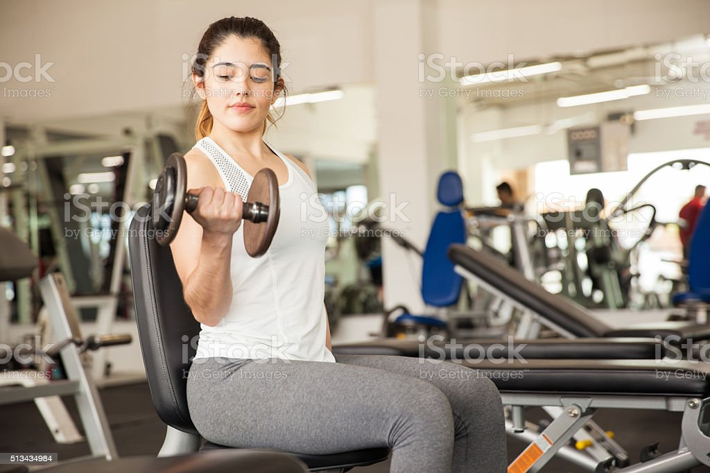 Beautiful girl doing bicep curls at the gym stock photo