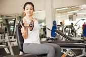 Beautiful girl doing bicep curls at the gym
