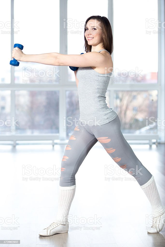 Beautiful girl doing fitness exercises with dumbbells stock photo