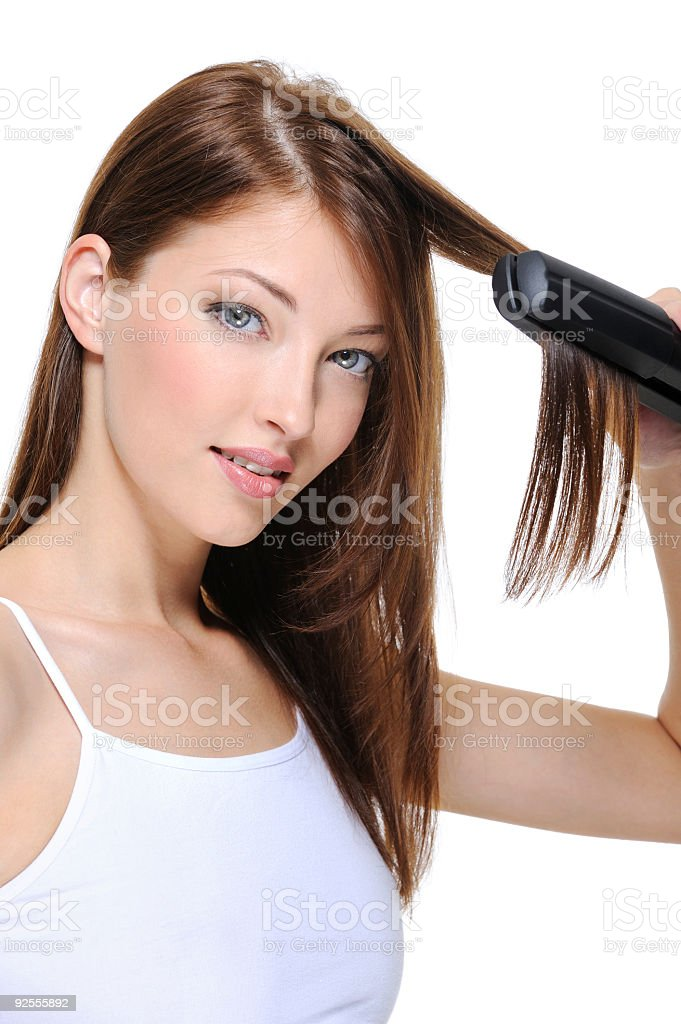 beautiful girl doing hairstyle with hair iron royalty-free stock photo
