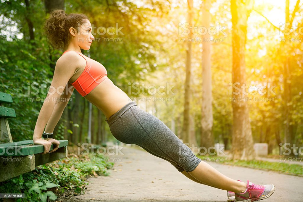 Beautiful girl doing push ups outdoor stock photo