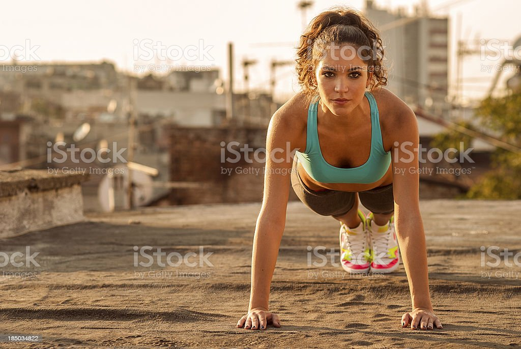 beautiful girl doing push ups outdoors on the roof royalty-free stock photo