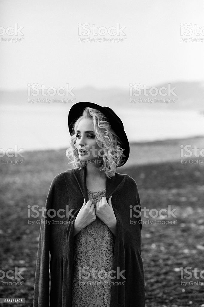 Beautiful girl dressed in old-fashioned coat and hat stock photo