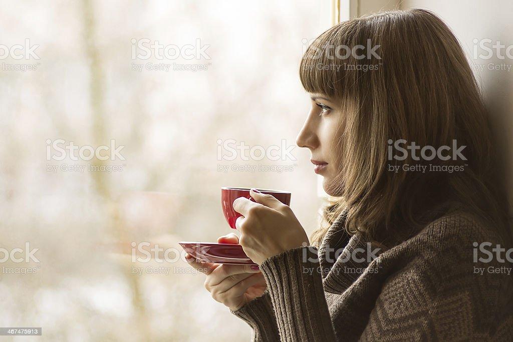 Beautiful girl drinking Coffee or Tea near Window stock photo