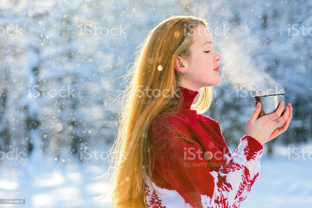 Beautiful girl drinking tea in winter woods royalty-free stock photo