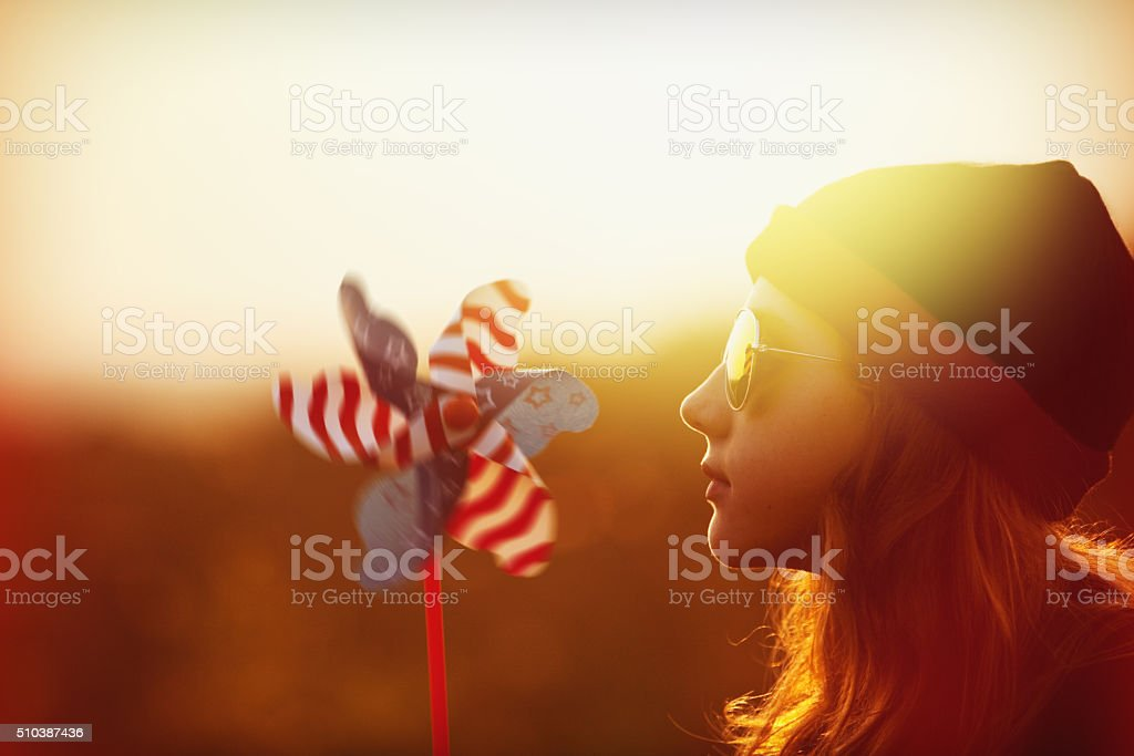 Beautiful Girl During Sunset With Pinwheel stock photo