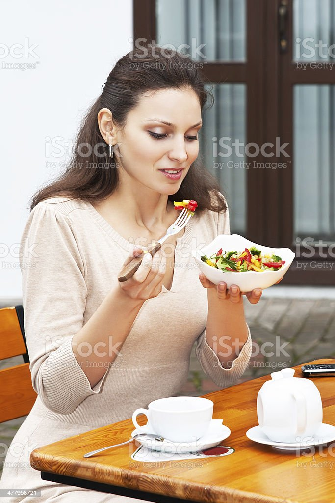 Beautiful girl eats vegetable salad royalty-free stock photo