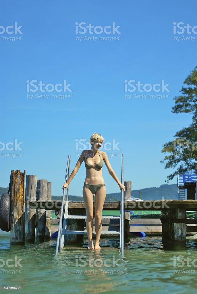 Beautiful girl entering water stock photo