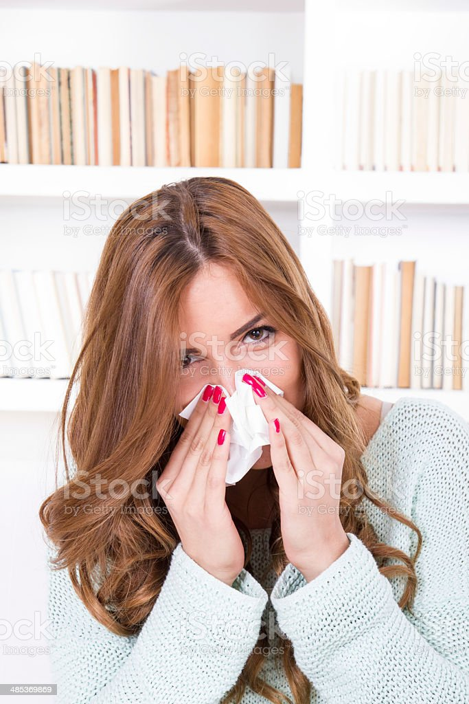 beautiful girl feeling ill caught cold sniffles blowing her nose royalty-free stock photo