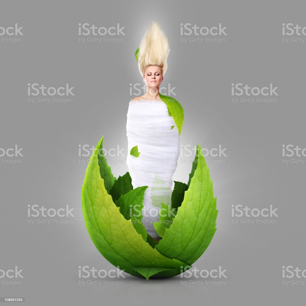 Beautiful girl grows from green leaves stock photo