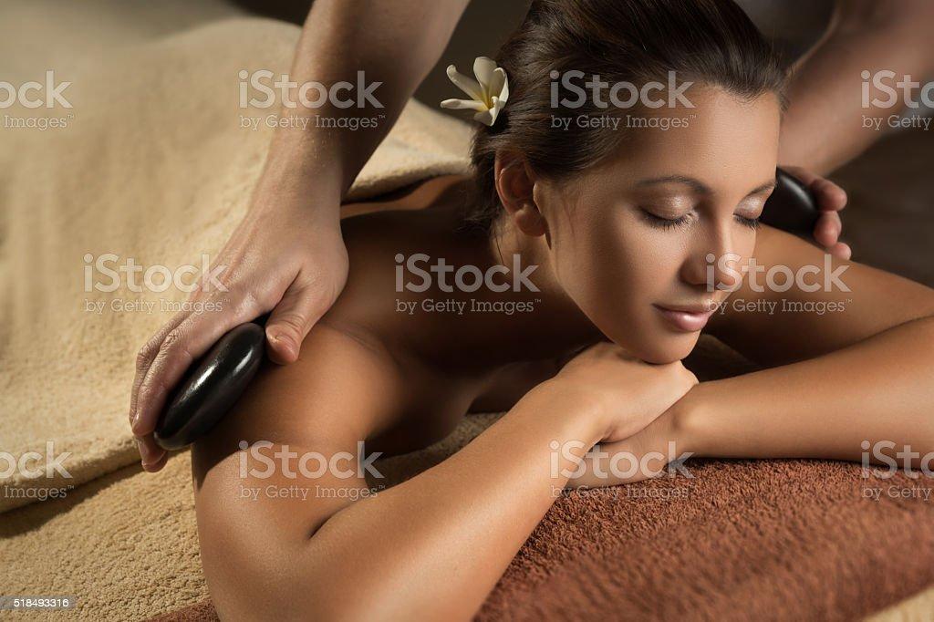 Beautiful girl has stone massage. stock photo