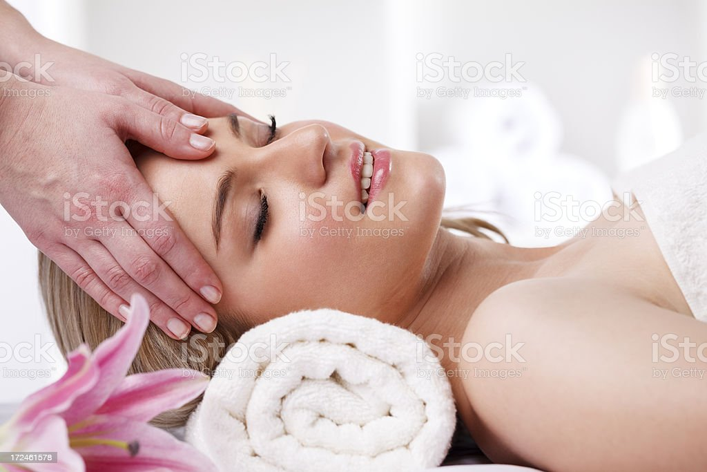 Beautiful girl having head massage at spa centre stock photo