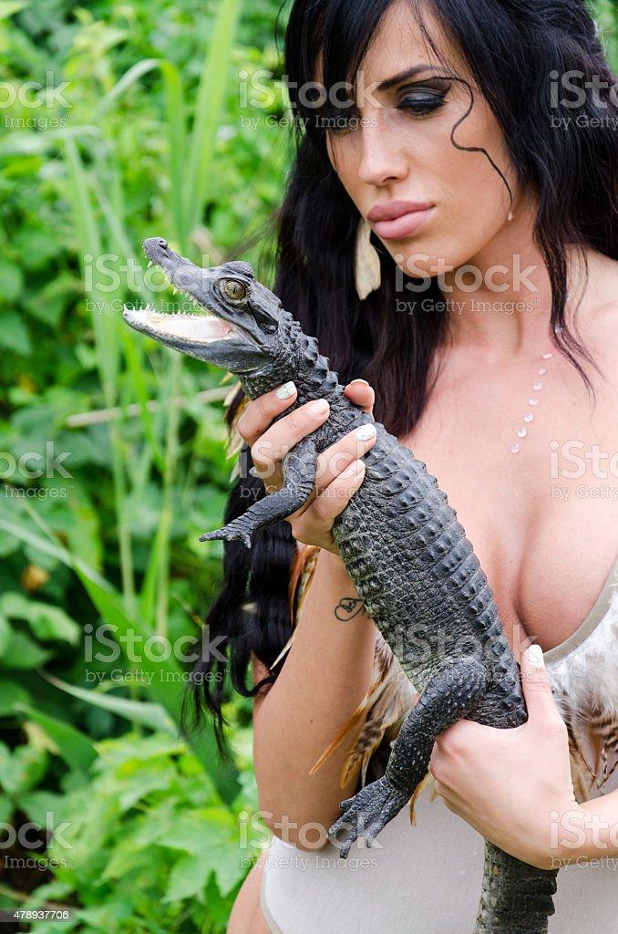 Beautiful girl holding a crocodile stock photo