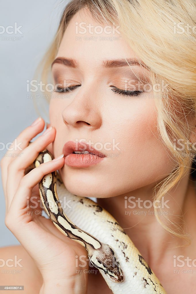 Beautiful girl  holding a python, which wraps around her body stock photo