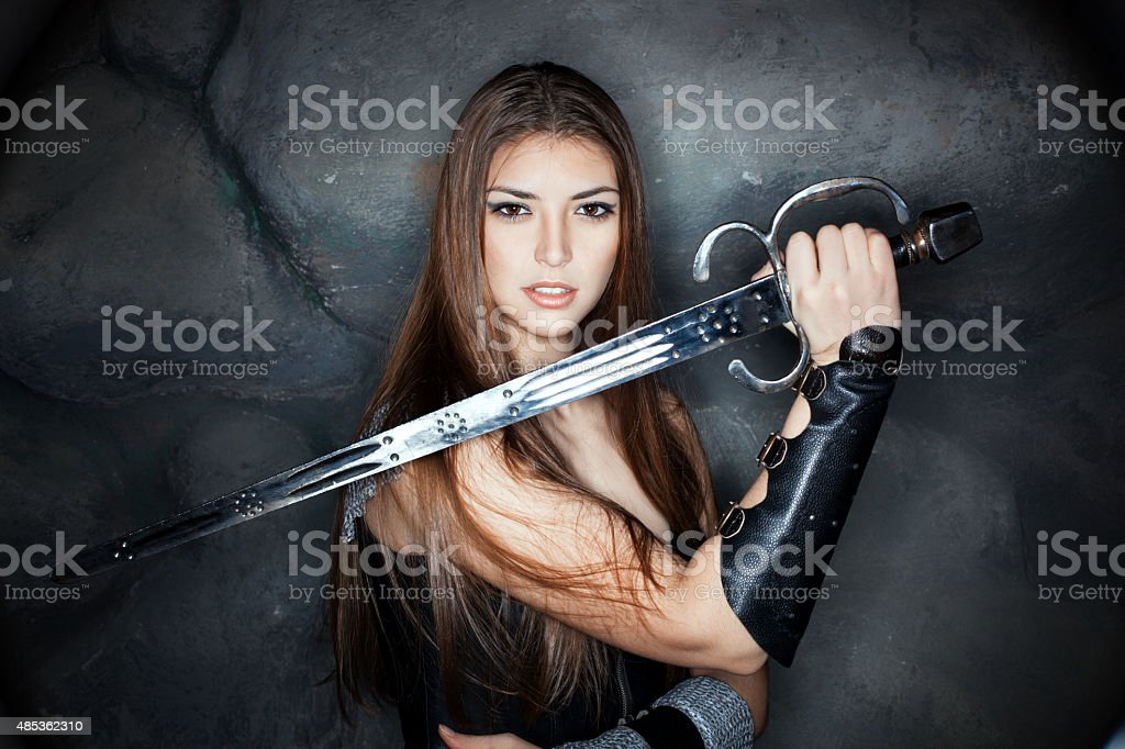 Beautiful girl holding a steel sword in his hand. stock photo