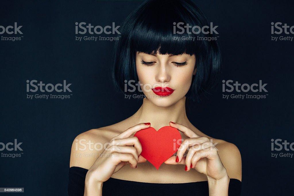 Beautiful girl holding artificial heart stock photo