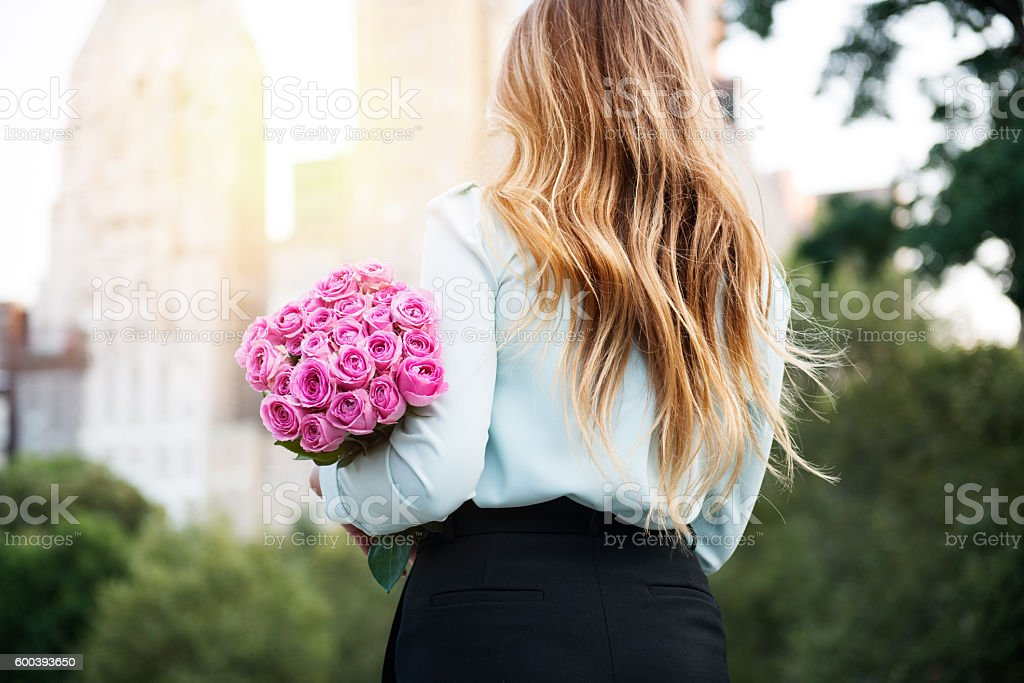 Beautiful girl holding bouquet of pink roses flowers on dating stock photo