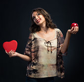 Beautiful girl holding heart and apple