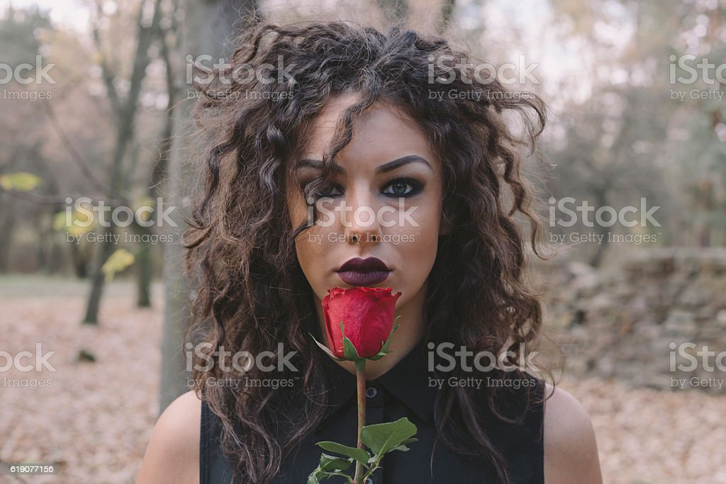 Beautiful girl holding red rose in front of her face stock photo