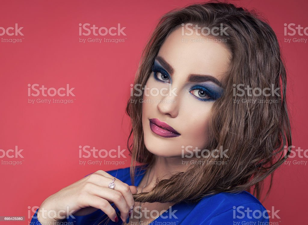 beautiful girl in a blue dress posing in studio stock photo