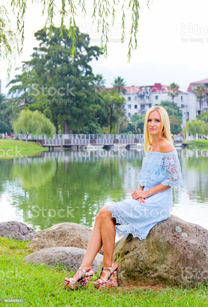 Beautiful girl in a blue dress siting on the stone by the lake. stock photo