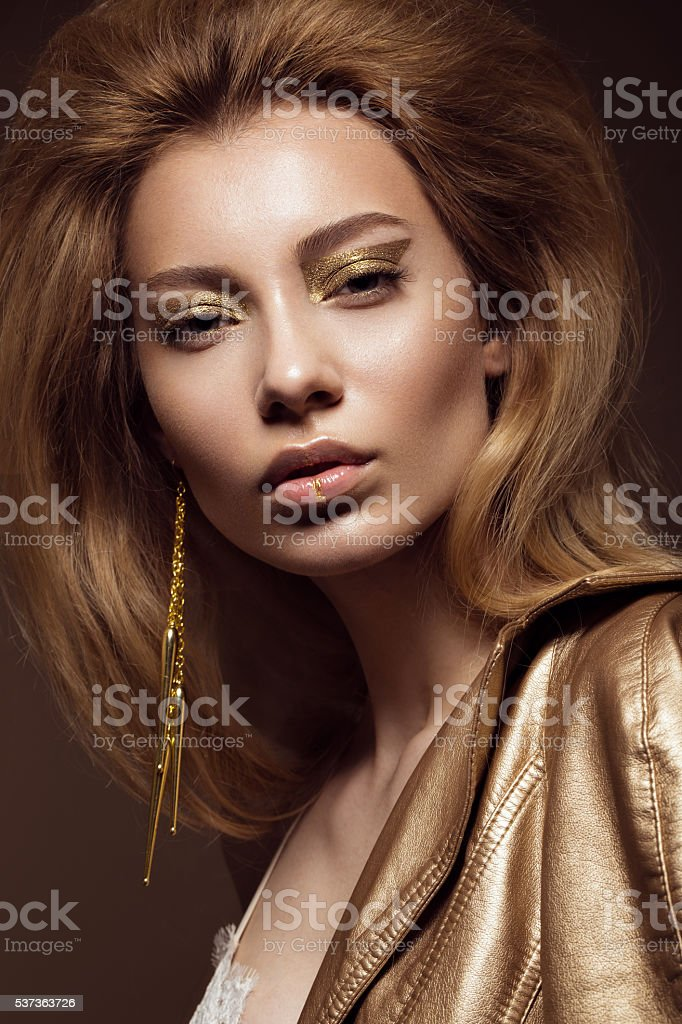Beautiful girl in a gold dress with creative makeup and stock photo