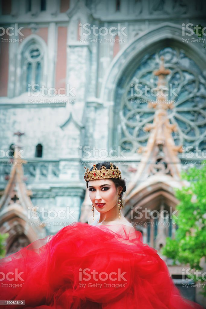 beautiful girl in a long red dress and royal crown stock photo