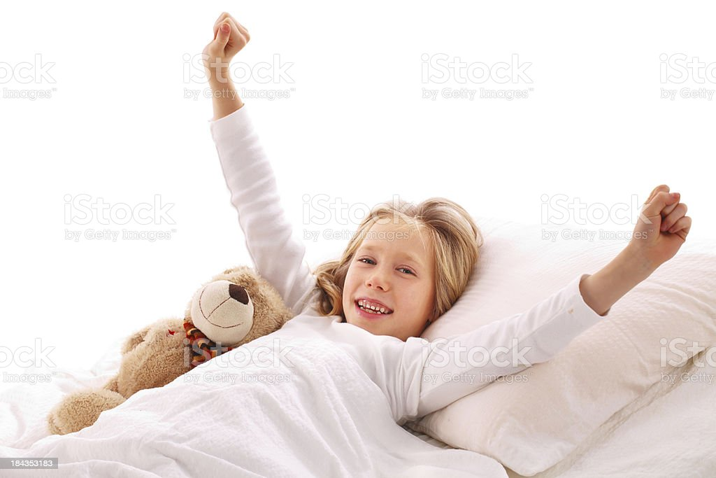 Beautiful girl in bed with her teddy bear. stock photo