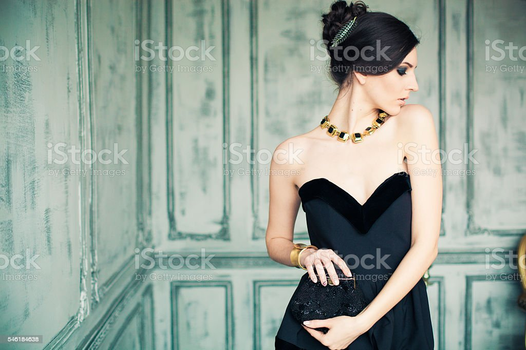 beautiful girl in black dress posing like diva stock photo