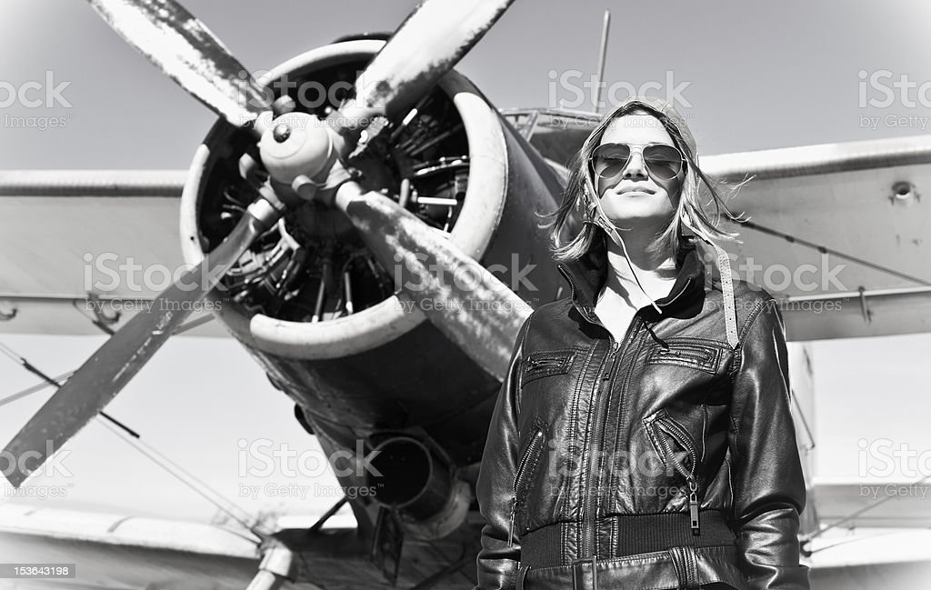 Beautiful girl in black jacket standing on a war aircraft. royalty-free stock photo