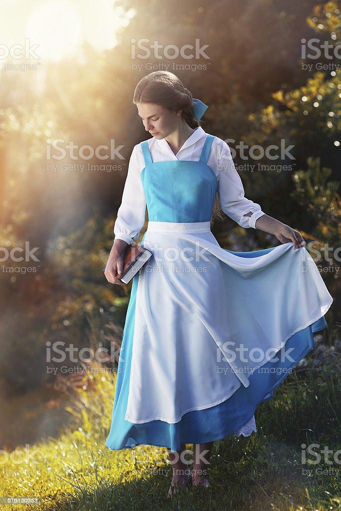 beautiful girl in cosplay Belle  in the sun stock photo