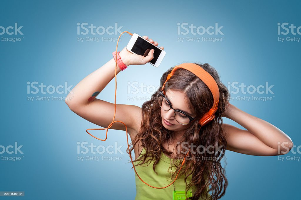 Beautiful girl in headphones listening to music and dancing stock photo