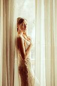 Beautiful girl in long dress standing near the window. Thinking