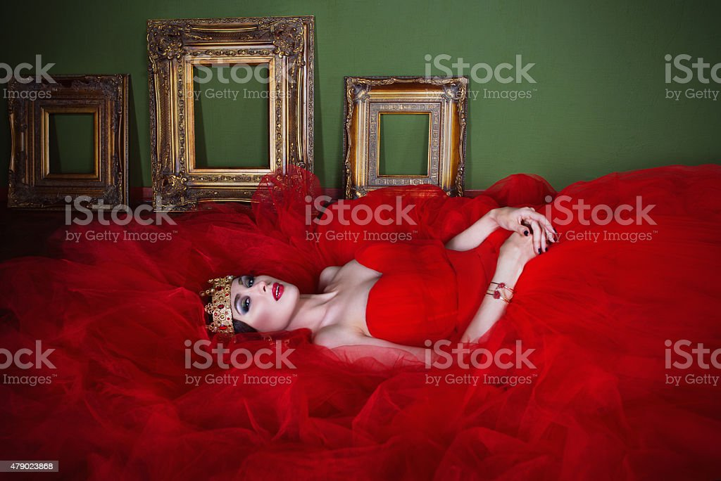 Beautiful girl in long red dress and in royal crown stock photo