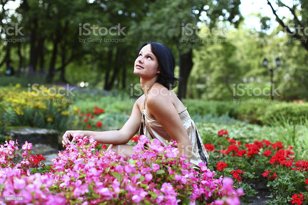 Beautiful girl in park with colorful flowers stock photo