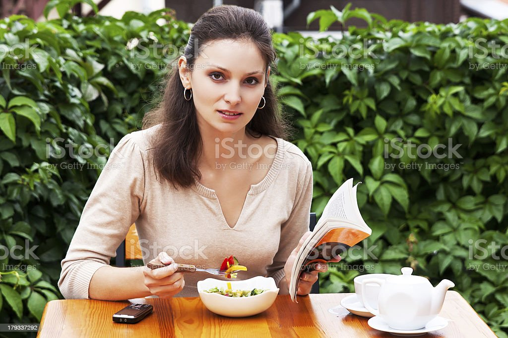 Beautiful girl in  summer cafe reading  book royalty-free stock photo