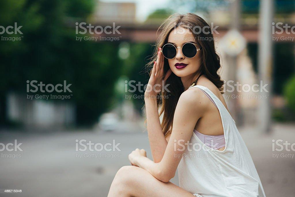 beautiful girl in sunglasses sitting stock photo