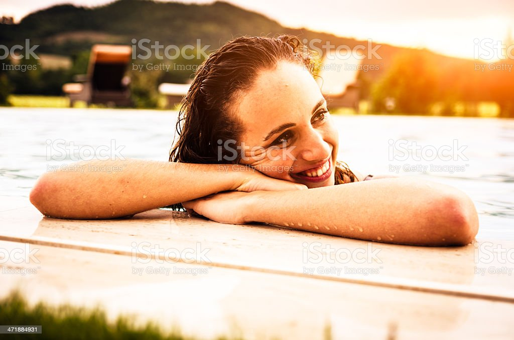 Beautiful girl in swimming pool at sunset royalty-free stock photo