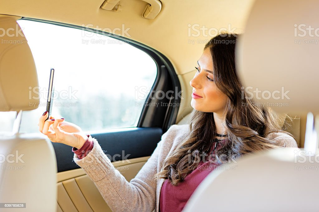 Beautiful girl in the backseat of the limousine stock photo