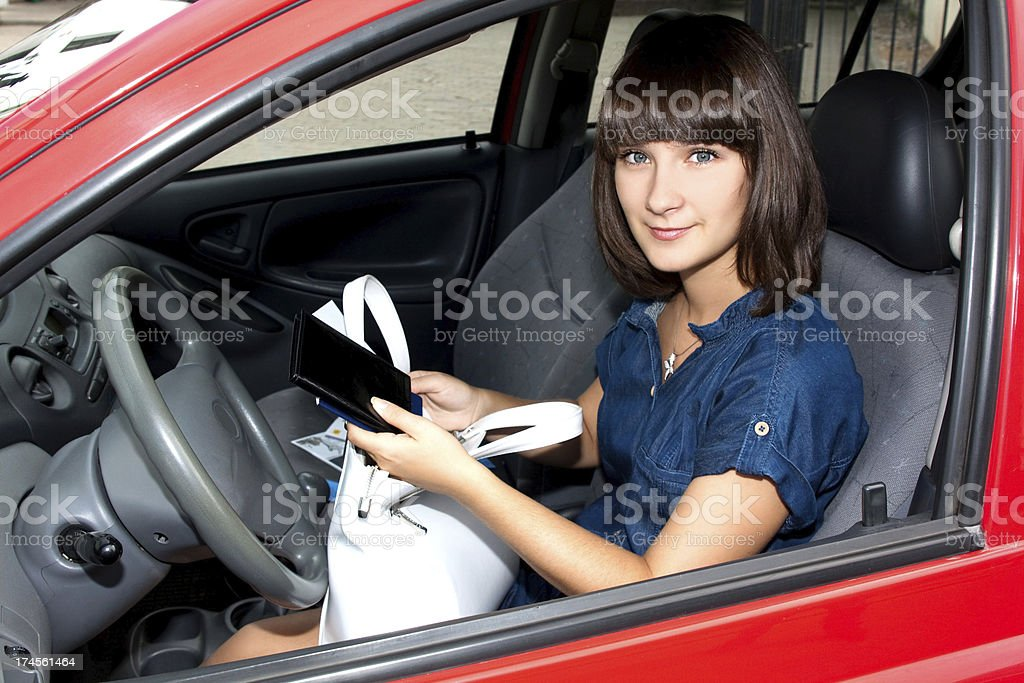 Beautiful girl in the car with documents stock photo