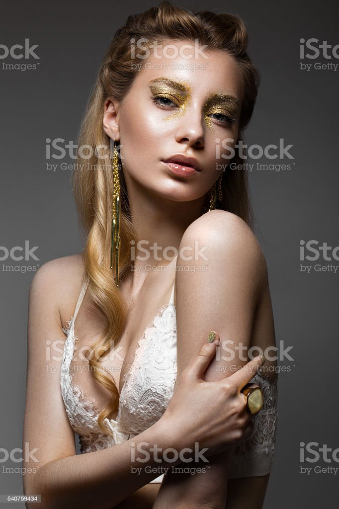 Beautiful girl in Underwear with creative gold makeup and hair. stock photo
