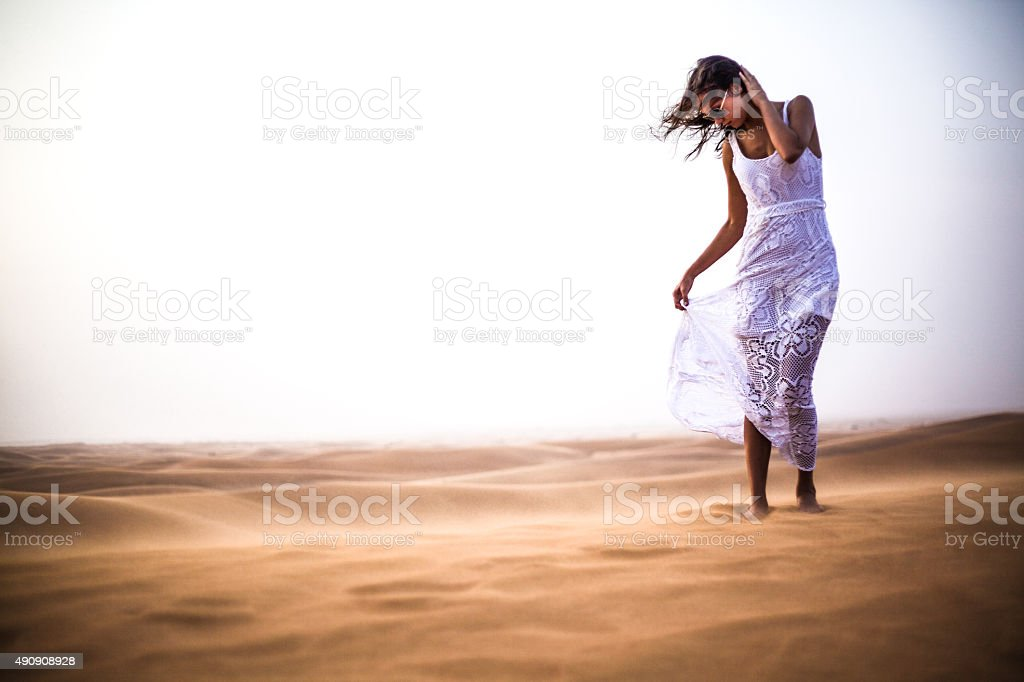 Beautiful Girl in White Dress braving the harsh desert stock photo