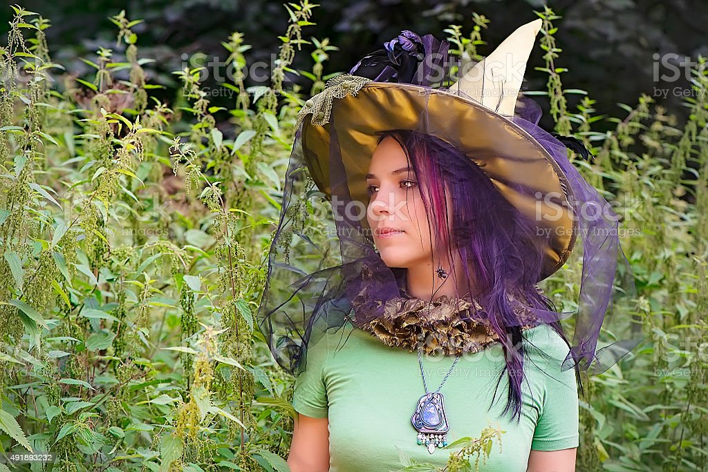 Beautiful girl in witch hat stock photo