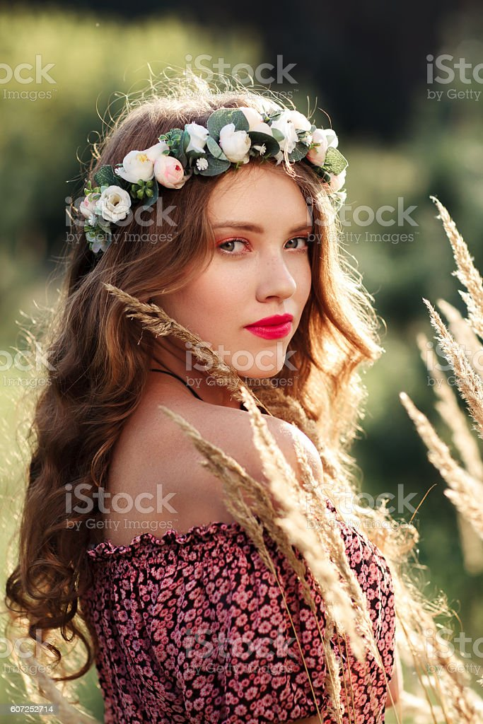 Beautiful girl in wreath standing near spikelets stock photo