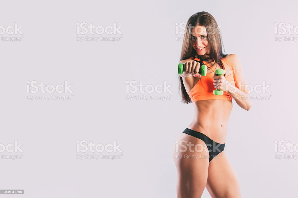 Beautiful girl is engaged in fitness with dumbbells. stock photo