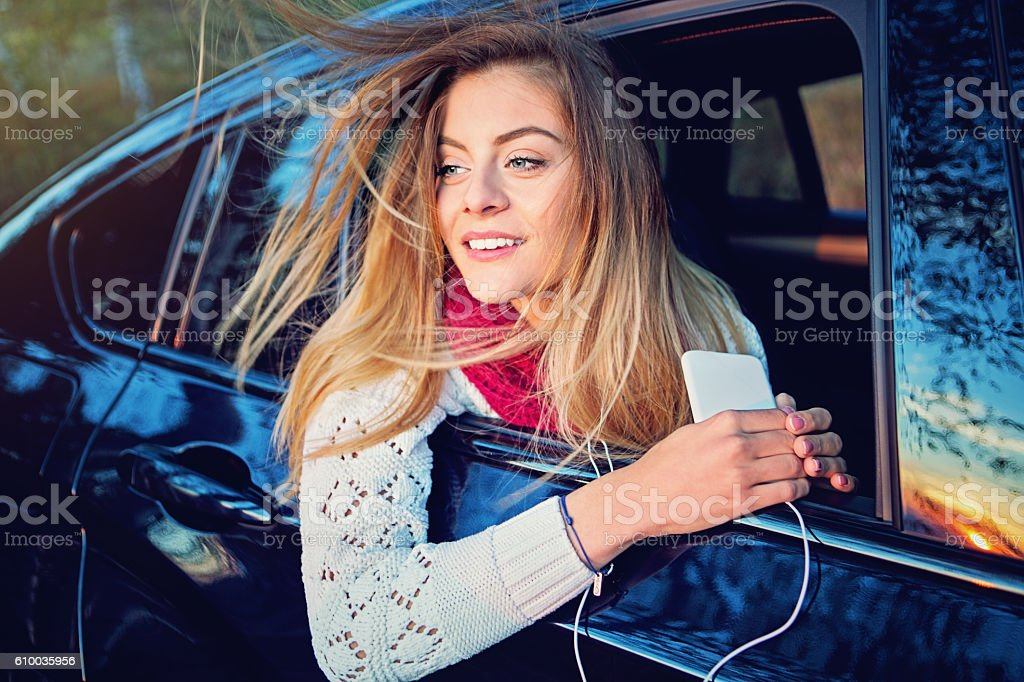 Beautiful girl is listening the music in the car stock photo