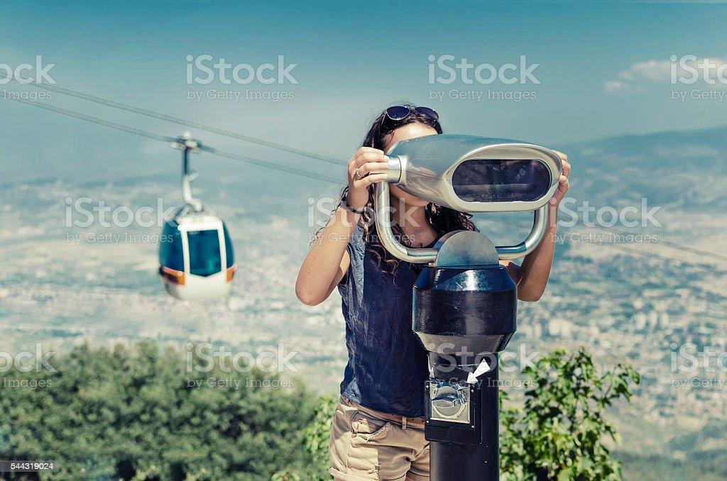 Beautiful girl  is looking at coin operated binocular stock photo