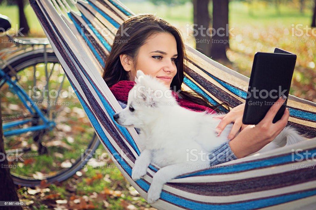 Beautiful girl is reading e-book in the hammock stock photo