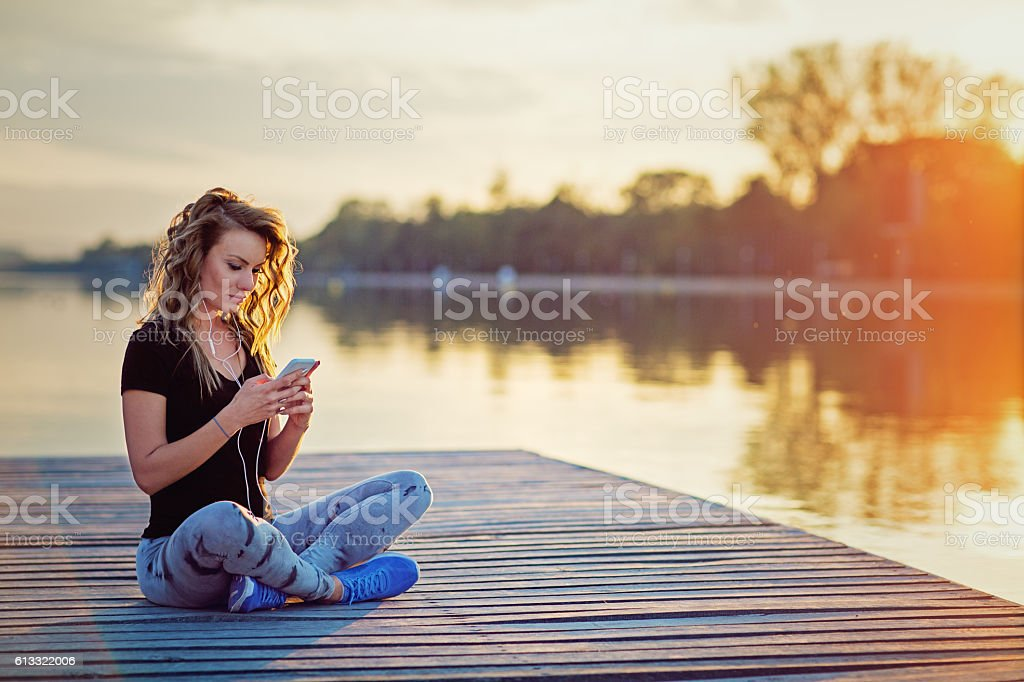 Beautiful girl is texting and listening the music stock photo