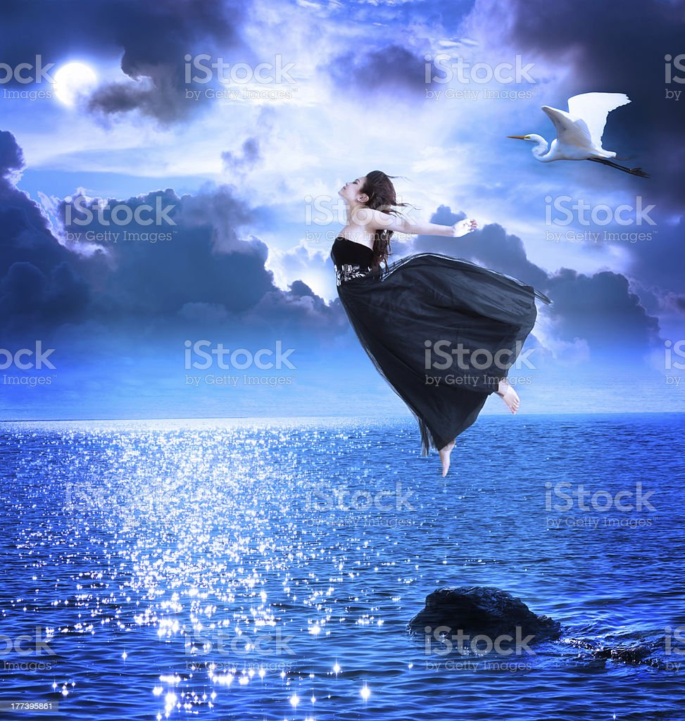 Beautiful girl jumping into the blue night sky stock photo